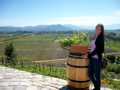 Posing with a Pinot Noir Vine and the vineyard in the background!